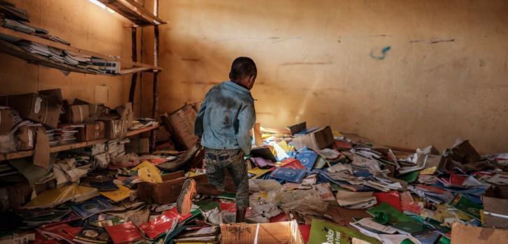 Un niño camina entre los restos de una biblioteca de una escuela primaria que fue dañada durante la crisis que irrumpió en la villa de Bisover en la región de Tigray, en Etiopía