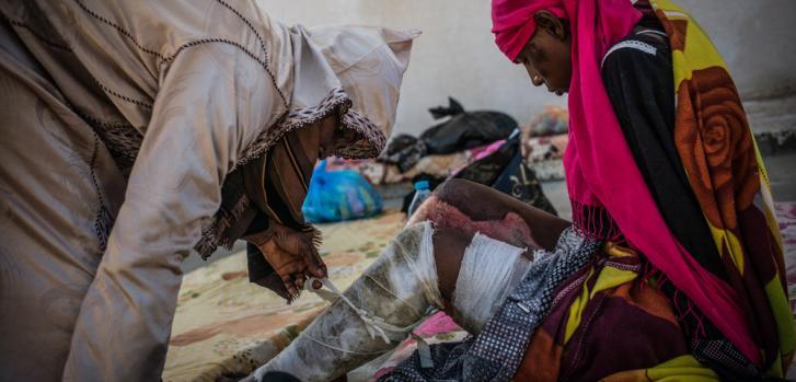 """""""La mujer del pañuelo rosa"""" en el centro de detención para mujeres en Sorman, al oeste de Tripoli, en Libia; en la foto está siendo atendida por otra detenida."""
