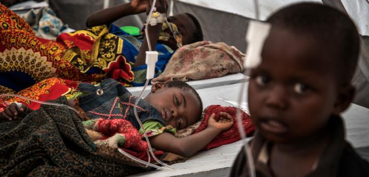 En el Centro de Tratamiento del Cólera en Minova, las filas de camas están llenas de niños recostados o sentados solos mientras sus madres entran y salen de la carpa; algunas lavan la ropa, otras tratan de alentar a sus hijos a tomar agua. © Arjun Claire