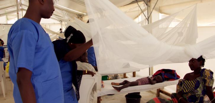 Ayesha y John, miembros del equipo de salud de MSF hablan con Khadija, una paciente con sospecha de padecer el cólera.