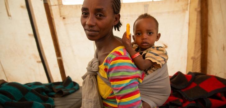 Una madre lleva a su hijo boca arriba en el centro de salud que apoyamos en Banko Gotiti, en el área de Gedeo, en el sur de Etiopía, donde el niño se está recuperando de la desnutrición.