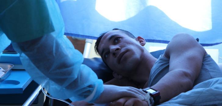 Ruslan, de 24 años, junto a una enfermera de Médicos Sin Fronteras en la habitación de aislamiento en un hospital en Khan Younis, Gaza. Está recibiendo tratamiento por una infección resistente a los antibióticos en los huesos de sus piernas, después recib