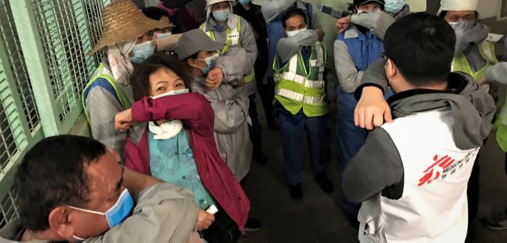 """May Chan (en rojo), una limpiadora de calles en Hong Kong, asiste a la sesión de promoción de la salud de MSF sobre el nuevo coronavirus. """"Es la primera vez que me doy cuenta de que si toso sin pañuelo, debería toser en mi codo pero no en mis manos."""""""