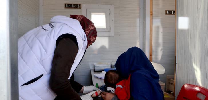 Una mujer siria desplazada junto a su hijo siendo atendido por desnutrición en la clínica móvil de Médicos Sin Fronteras en el campamento de Qadimoon, al noroeste de Siria.