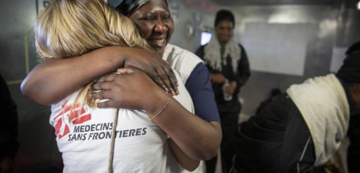 Abrazo a bordo del Ocean Viking en febrero de 2020, mientras los sobrevivientes, rescatados en el mar Mediterráneo, escuchaban la noticia de que finalmente podrían abandonar el barco ya que se había asignado un lugar seguro para desembarcar en Italia.