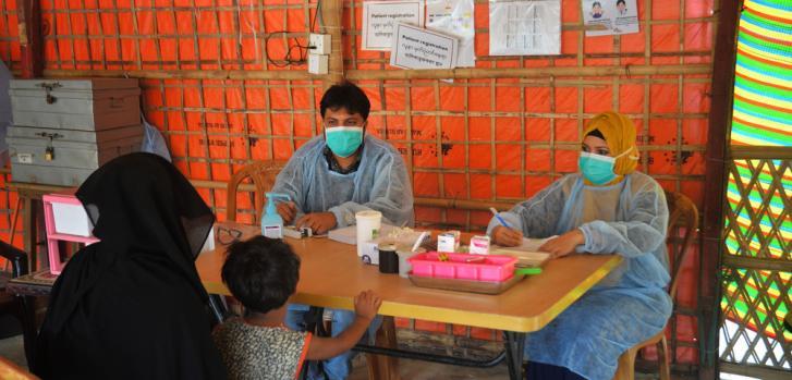 Nazrul Islam, asistente médico, y Mahabuba Khatun, auxiliar de enfermería, evalúan a un paciente en la clínica de atención primaria de Jamtoli en los campos de refugiados de Cox's Bazar, Bangladesh.