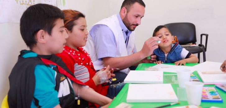 Un día en el centro de talasemia de Zahle, Líbano. Bouchra, de rojo, y otros dos niños con talasemia juegan en el centro de tratamiento de MSF con uno de sus doctores.