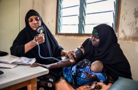Salma, enfermera de MSF, controlando la presión arterial de una madre con diabetes que ha llevado a su hijo a la clínica.
