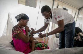 Médico revisando niño epidemia sarampión