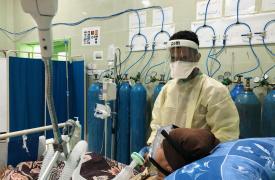 Médico de MSF trabajando en la unidad de cuidados intensivos junto a una paciente con COVID-19 en estado crítico. Hospital Al Gamhouria, Aden, Yemen. Marzo de 2021.