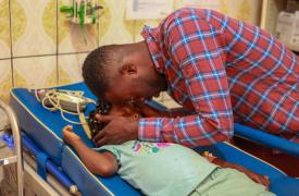 Collins consuela a su hija y la distrae para evitar que vea cómo nuestros equipos le extraen un pedazo de vidrio del pie en Bamenda, Camerún. Noviembre de 2020