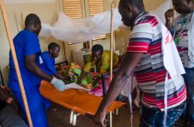 Un paciente en la sala de cirugía del hospital de Bangassou es transportado, por personal de MSF y local, de vuelta a su cama. ©Natacha Buhler/MSF