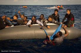 Una persona en el agua, apenas sostenida de uno de los tres botes de goma sobrecargado que fueron rescatados en la jornada del 1 de noviembre de 2017 por Médicos Sin Fronteras y SOS Mediterrane en el Mar Mediterráneo