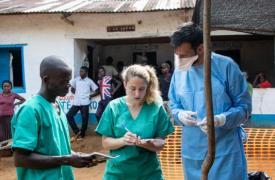La doctora Pauline Vetter, Luis Encinas y Josué, promotor de la salud, discuten el caso de un niño pequeño, contacto de un paciente de Ébola y que muestra signos de fiebre, en Ikoko, en República Democrática del Congo (junio de 2018)