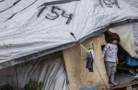 Una niña se asoma desde su carpa en el campo de refugiados de Moria, en la isla de Lesbos, Grecia.