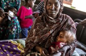 Husna Usman Mohamed, de 25 años, sosteniendo a su bebé Mohamed Sami, de casi 2 años, que fue admitido al hospital pediátrico de El Fasher, en Sudán.