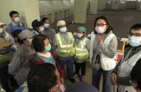El equipo de Médicos Sin Fronteras llevando a cabo una sesión de educación sanitaria con limpiadores de calles en Hong Kong sobre la importancia de las medidas de prevención, como lavarse las manos con frecuencia y usar adecuadamente las máscaras faciales