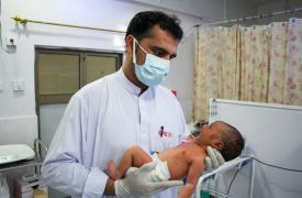 Un enfermero de Médicos Sin Fronteras con un bebé en la unidad de recién nacidos del hospital de la sede del distrito de Timergara, Pakistán.