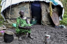 Una mujer joven sentada frente a su refugio en Lukurunyang después de que las fuertes lluvias destruyeran sus cultivos.