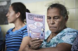 Una mujer lee un folleto de concientización acerca de la violencia. ©Christina Simons/MSF