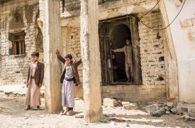 Niños frente a su casa bombardeada en Yemen